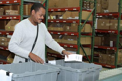 Worker filling bins at our Rock Creek distribution center